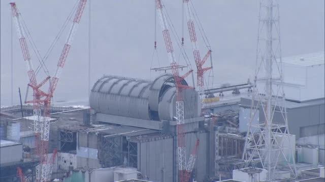 work was completed feburary 21,japan,on a half-cylinder roof designed to trap radioactive substances emitted when spent fuel rods are removed from... - nuclear energy点の映像素材/bロール