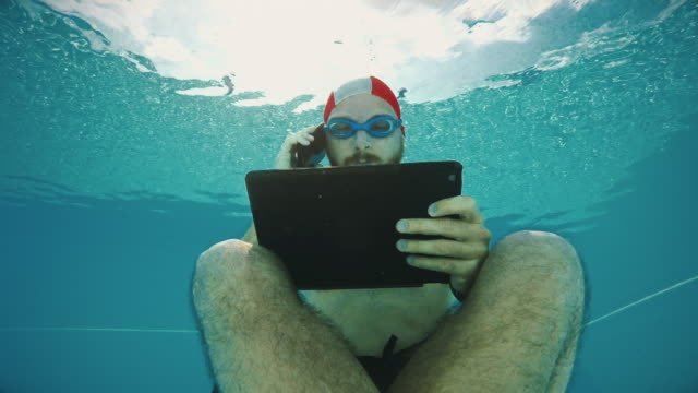 Workaholic man underwater con tablet y móvil
