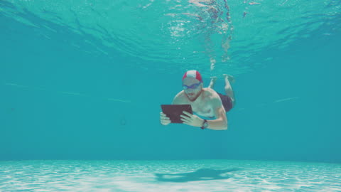 workaholic man using tablet underwater in a swimming pool - bizarre stock videos & royalty-free footage