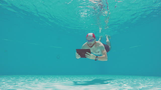 Workaholic man using tablet underwater in a swimming pool