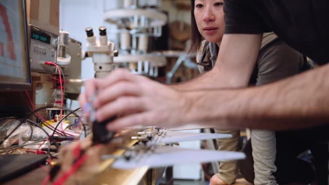 worker adjusting wiring on robotics circuit boards - vanguardians stock videos & royalty-free footage