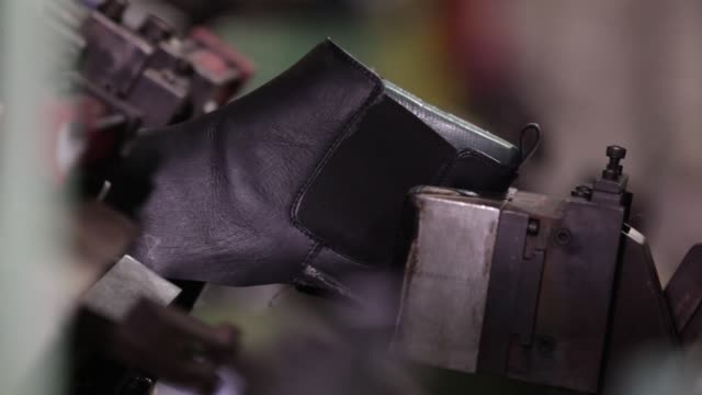 CU worker affixes a leather upper to a last on the production line at a Virola Shoes Pvt manufacturing facility in Agra Uttar Pradesh India on...