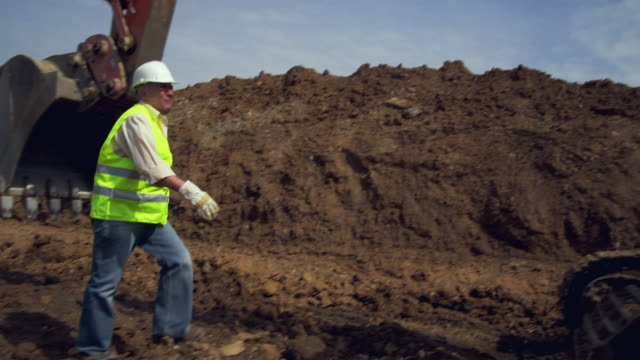 ws pan worker approaching and then entering cab of excavator / malaga, andalusia, spain - bagger stock-videos und b-roll-filmmaterial