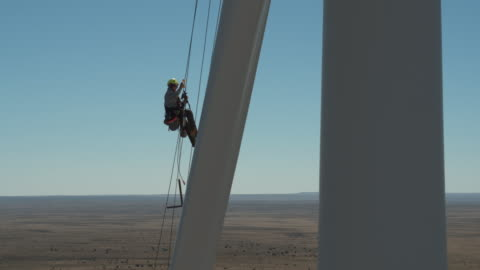 worker ascending a rope on a turbine blade - wind turbine stock videos & royalty-free footage