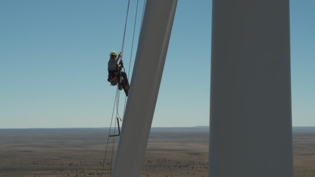 worker ascending a rope on a turbine blade - imbracatura di sicurezza video stock e b–roll