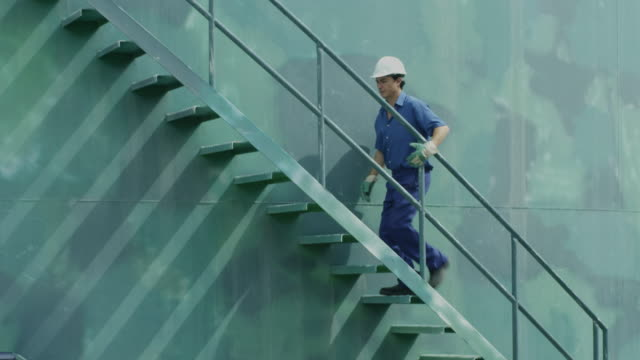 LS worker ascending stairs on storage tank; camera follows him up, RED R3D 4K