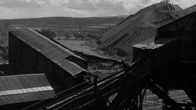 montage worker at a colliery at the top of a plate conveyor carrying dirt breaking up large chunks or dumping them down below / wales, united kingdom - coal stock videos & royalty-free footage