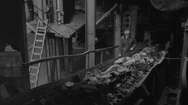 HA Worker at a colliery walking alongside a plate conveyor carrying dirt / Wales, United Kingdom