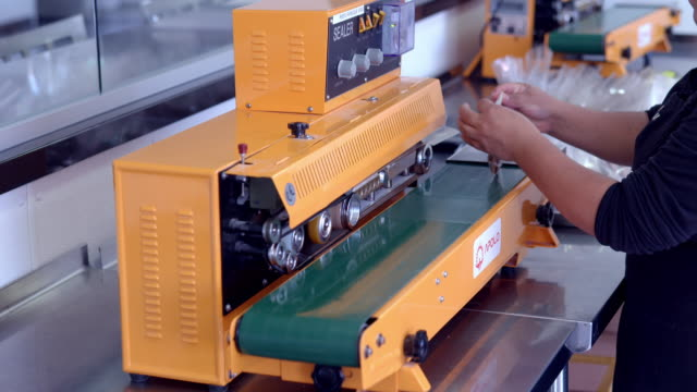 cu worker at candy factory runs small plastic bag through sealer machine / rancho mirage, california, usa - rancho mirage stock videos & royalty-free footage