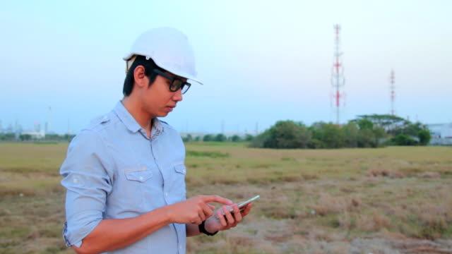 Lavoratore in impianto industriale lavorando su uno smartphone.