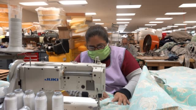 a worker at northcape an outdoor furniture manufacturer makes personal protective equipment at a sewing machine during the coronavirus pandemic on... - untersuchungskittel stock-videos und b-roll-filmmaterial