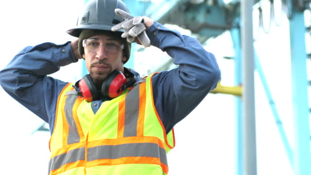 worker at shipping port near crane, puts on hardhat - helmet stock videos & royalty-free footage
