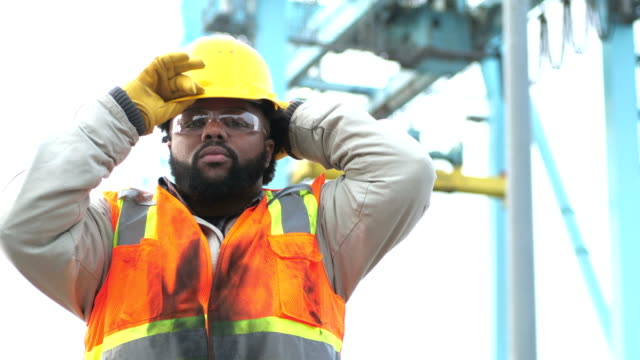 worker at shipping port near crane, puts on hardhat - safety stock videos & royalty-free footage