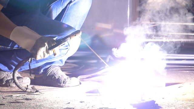 Worker at the industrial factory welding steel structure with sparks