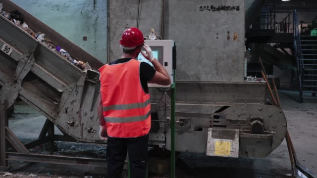 worker at waste disposal dump controlling conveyor belt speed on touch screen - environmental cleanup stock videos & royalty-free footage