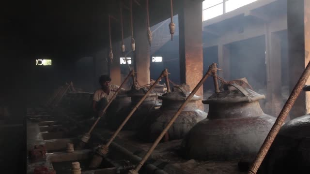 a worker attaches a pipe to a copper still as the furnace is lit and smoke slowly builds up at a pragati aroma oil distillers pvt factory in kannauj... - uttar pradesh stock videos and b-roll footage