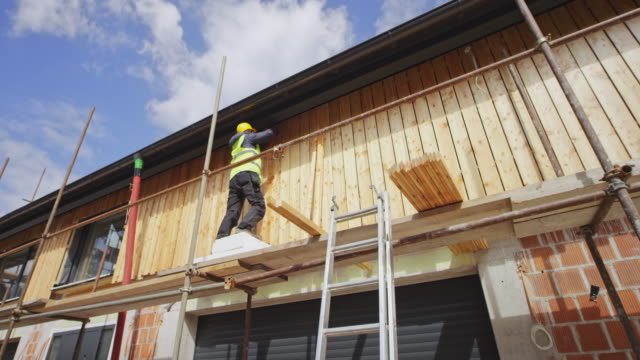 cs worker attaching long vertical planks for the façade of the house - only mature men stock videos & royalty-free footage