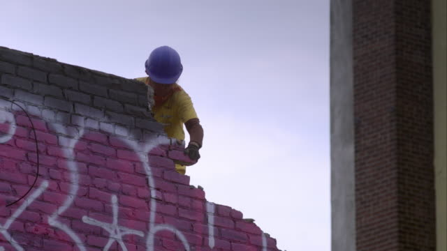 Worker bangs brick wall with her sledgehammer, removing small pieces as part of building demolish process.