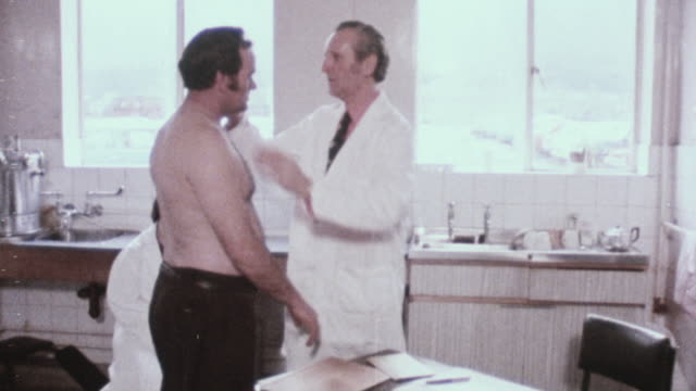 1978 montage worker being escorted from a waiting room to a doctor's office where he is being examined / united kingdom - examining stock videos & royalty-free footage