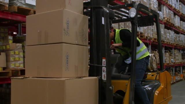 vídeos de stock, filmes e b-roll de empilhadeira de embarque trabalhador em armazém - caixa de papelão