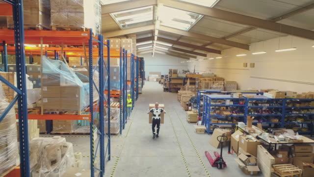 vídeos y material grabado en eventos de stock de trabajador trayendo una caja grande en el almacén. usando exoesqueleto accionado. vista aérea - material médico