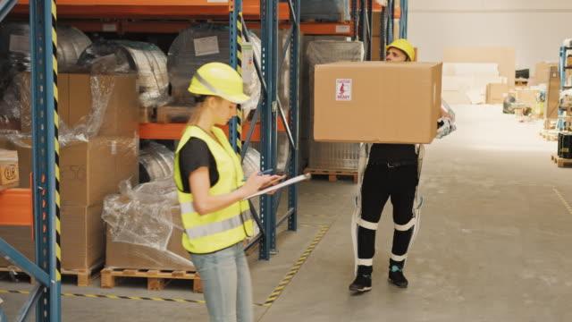 arbeiter bringt große box in das lager. tragen von motorisiertem exoskelett. luftbild - hubwagen stock-videos und b-roll-filmmaterial