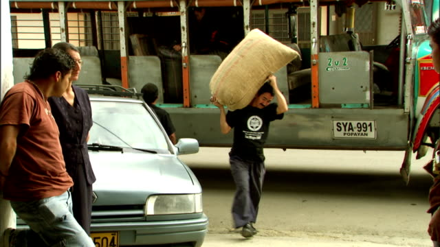 a worker carries a bag of coffee beans from a bus to a factory. - 麻袋点の映像素材/bロール
