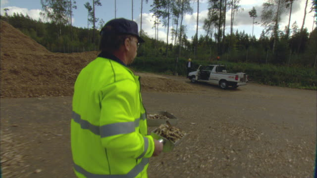 ms pov worker carrying samples of woodchips from biomass plant to truck / vaxjo, sweden - vaxjo stock videos & royalty-free footage