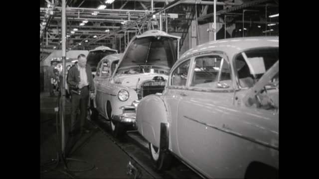 vídeos de stock e filmes b-roll de ms worker checking car on assembly line in factory / united states - 1950