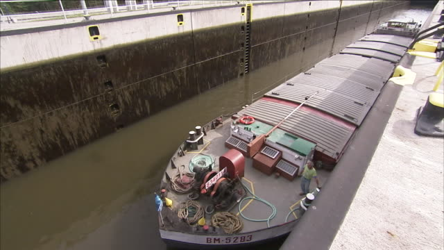 a worker checks a barge tethered at the dock of a water bridge. - chiusa di fiume video stock e b–roll