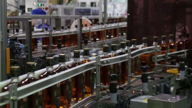 A worker checks a bottle of Black Nikka Clear whisky on the production line at Nikka Whisky Distilling Co Ltd factory in Kashiwa Chiba Prefecture...