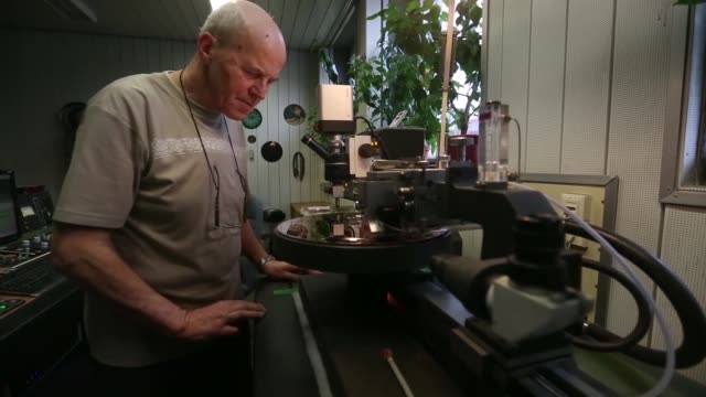 worker checks a dmm mastering machine, as the machine cuts the grooves onto the surface of a copper plate to create a metal master disc, used in the... - plant process stock videos & royalty-free footage