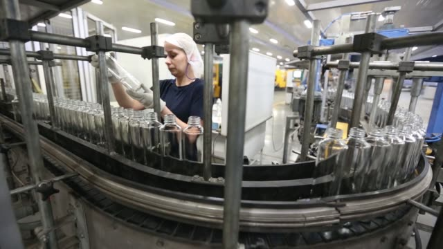 worker checks clear vodka bottles s for precise measurement during a quality control inspection at the ruscam kirishi ojsc glass manufacturing plant... - ウォッカ点の映像素材/bロール