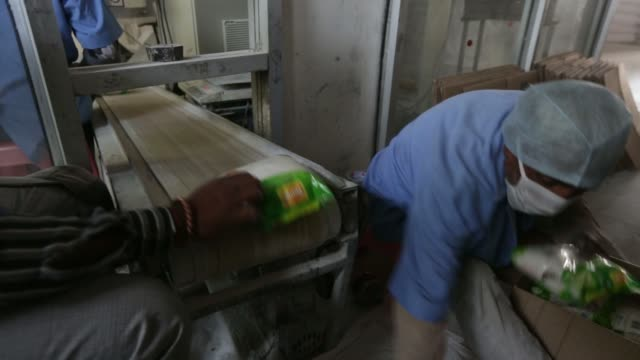 a worker checks the weight of packaged bags of refined sugar moving along a conveyor a worker pours refined sugar into a packaging machine - 砂糖点の映像素材/bロール