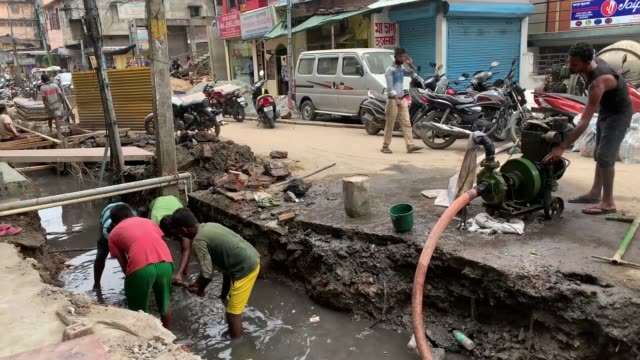 vídeos de stock, filmes e b-roll de october worker cleaning a drainage as they are working in a construction of a drain near a street in gauhati on 31 october 2020 - drenagem