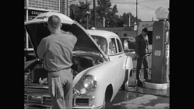 MS Worker cleaning car and refuelling at gas station / United States
