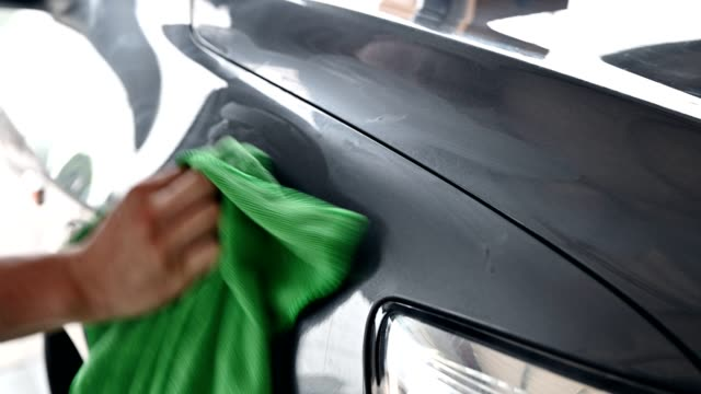 worker cleaning car with green microfiber cloth with scratch remover on hood - bonnet stock videos & royalty-free footage