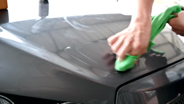 worker cleaning car with green microfiber cloth with scratch remover on hood - scratched stock videos & royalty-free footage