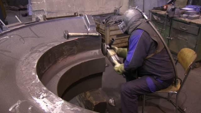 ms worker cleaning work pieces at foundry / junckerath, north rhine-westphalia, germany  - arbeiter stock-videos und b-roll-filmmaterial