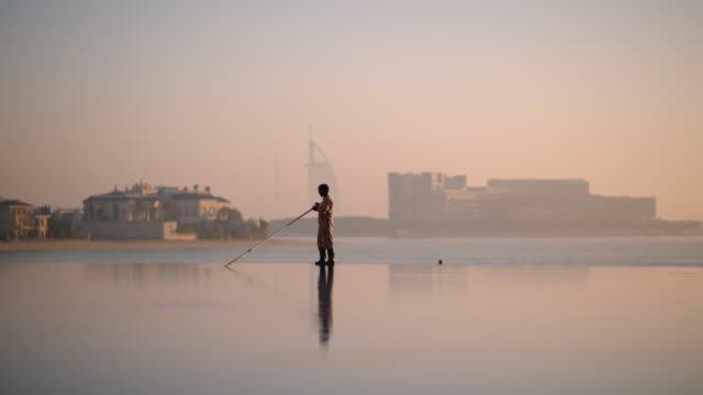 worker cleans pool at sunrise  - Palm Island, Dubai