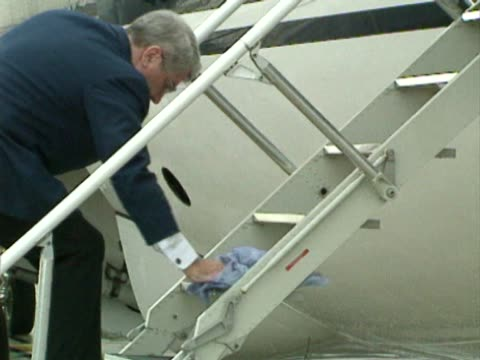 worker cleans the wet steps and handrails of the queens flight jet in preparation for the arrival of queen elizabeth ii before a flight from heathrow... - commercial aircraft stock videos & royalty-free footage