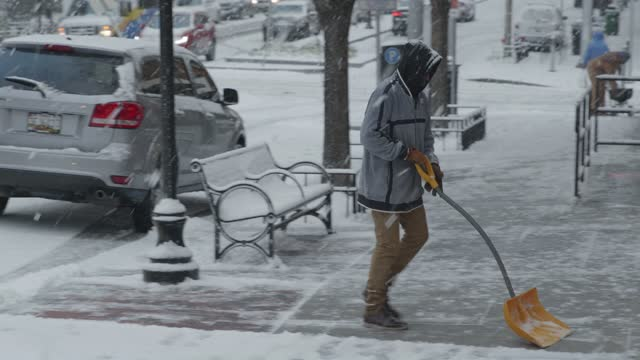 vidéos et rushes de worker clears away snow on a snowy sidewalk during winter storm gail on december 16, 2020 in baltimore, md. winter storm gail brings snow and ice to... - maryland état