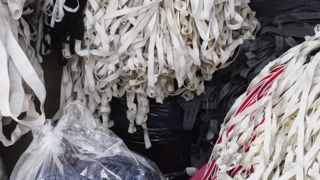 worker collecting something valuable from discarded fabric and elastics from a small garment factory in dhaka. - textilindustrie stock-videos und b-roll-filmmaterial