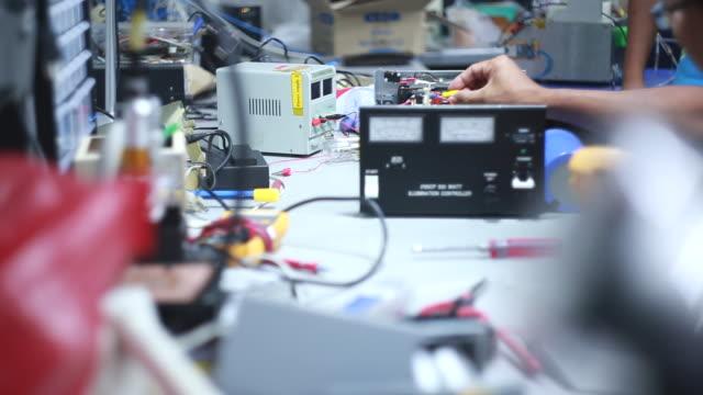 ein arbeiter kontrollen elektrische ausrüstung in einer fabrik mit moderner ausstattung - elektronik industrie stock-videos und b-roll-filmmaterial