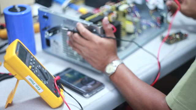 A worker controls electrical equipment on a factory with modern equipment