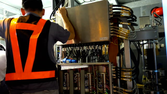 a worker controls electrical equipment on a factory with modern equipment - electrician stock videos and b-roll footage