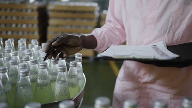 worker counting number of juice bottles in factory - pen stock videos & royalty-free footage