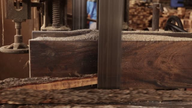a worker cuts lumber using a bandsaw at a sawmill of the eiwlee industrial co wood factory in pongyangkok lampang province thailand on friday oct 6... - timber yard stock videos & royalty-free footage