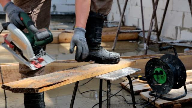労働者は、円形のこぎりで板をカットします。 - 尖っている点の映像素材/bロール