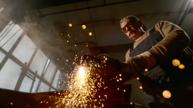 SLO MO Worker cutting through metal in the workshop